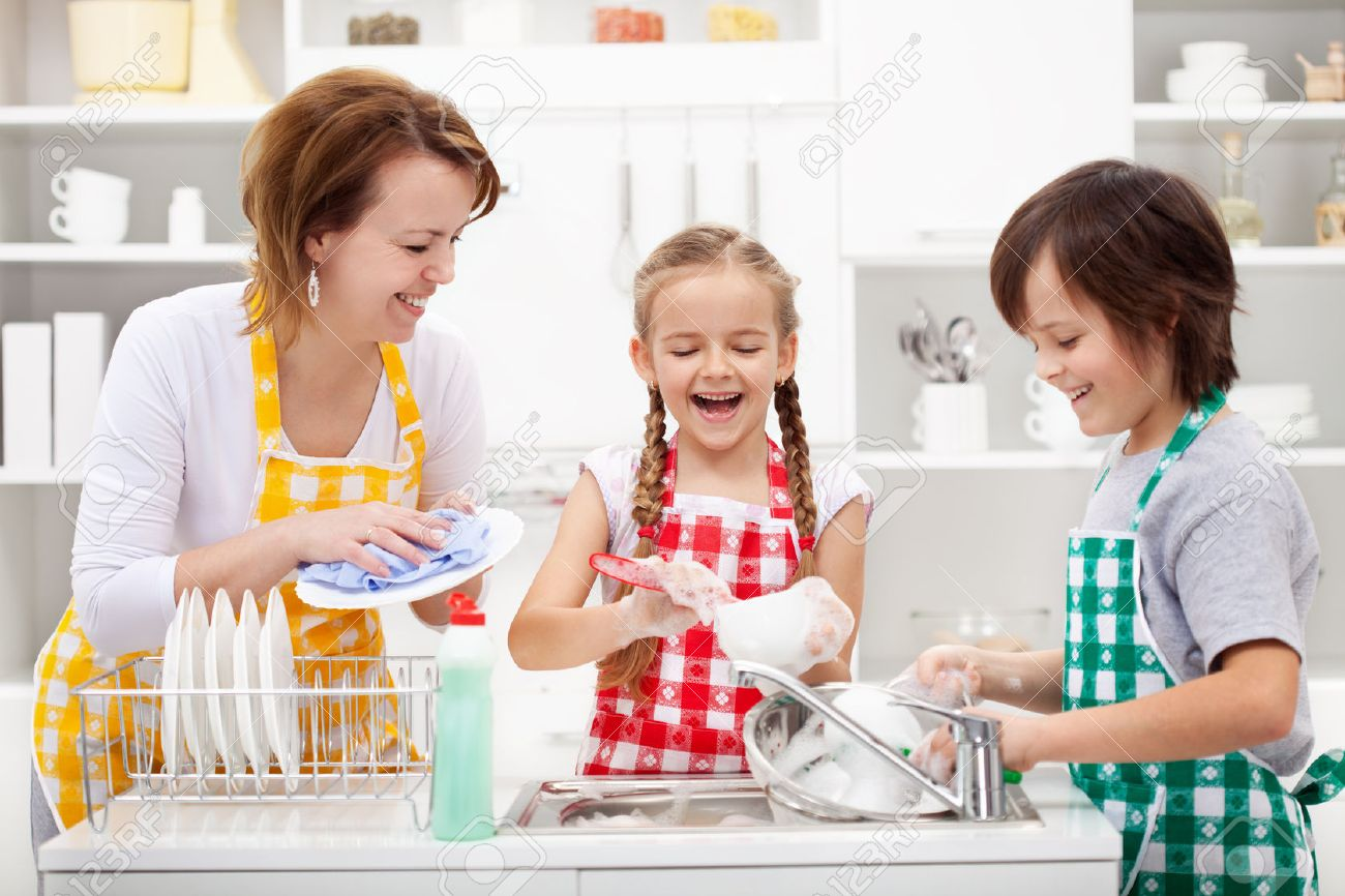 Kids and mother washing dishes - having fun together in the kitchen - 25986163