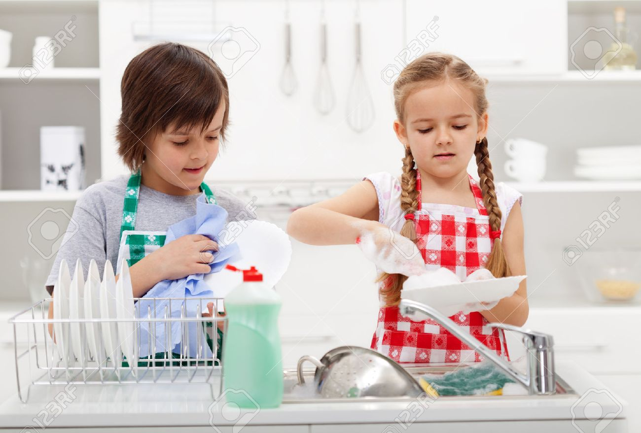Kids washing the dishes in the kitchen together - helping out with the home chores - 26398482