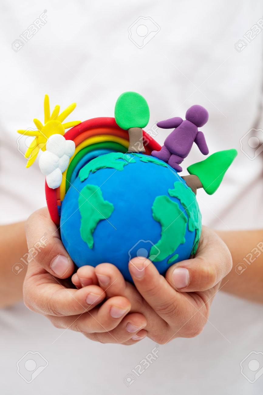 Modelling clay earth with rainbow and trees in child hands - 26398515
