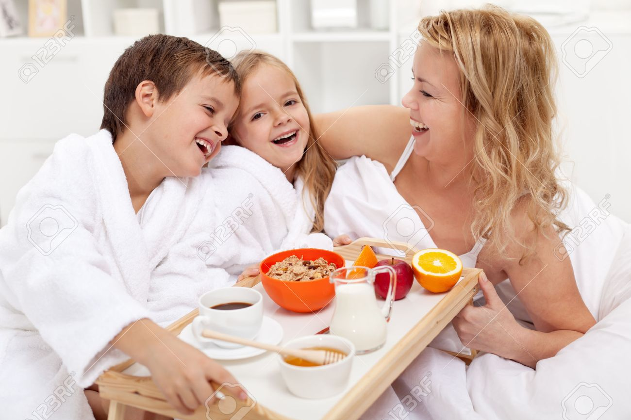 Happy morning - breakfast in bed for mom, kids pampering their mother - 27424989