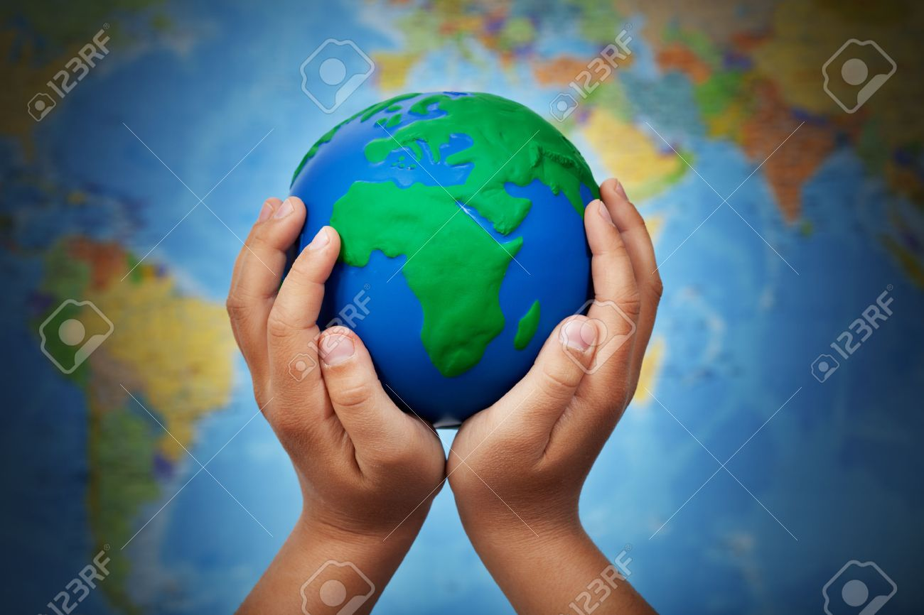 World Map On Hands.Ecology Concept With Earth Globe In Child Hands Against Blurry