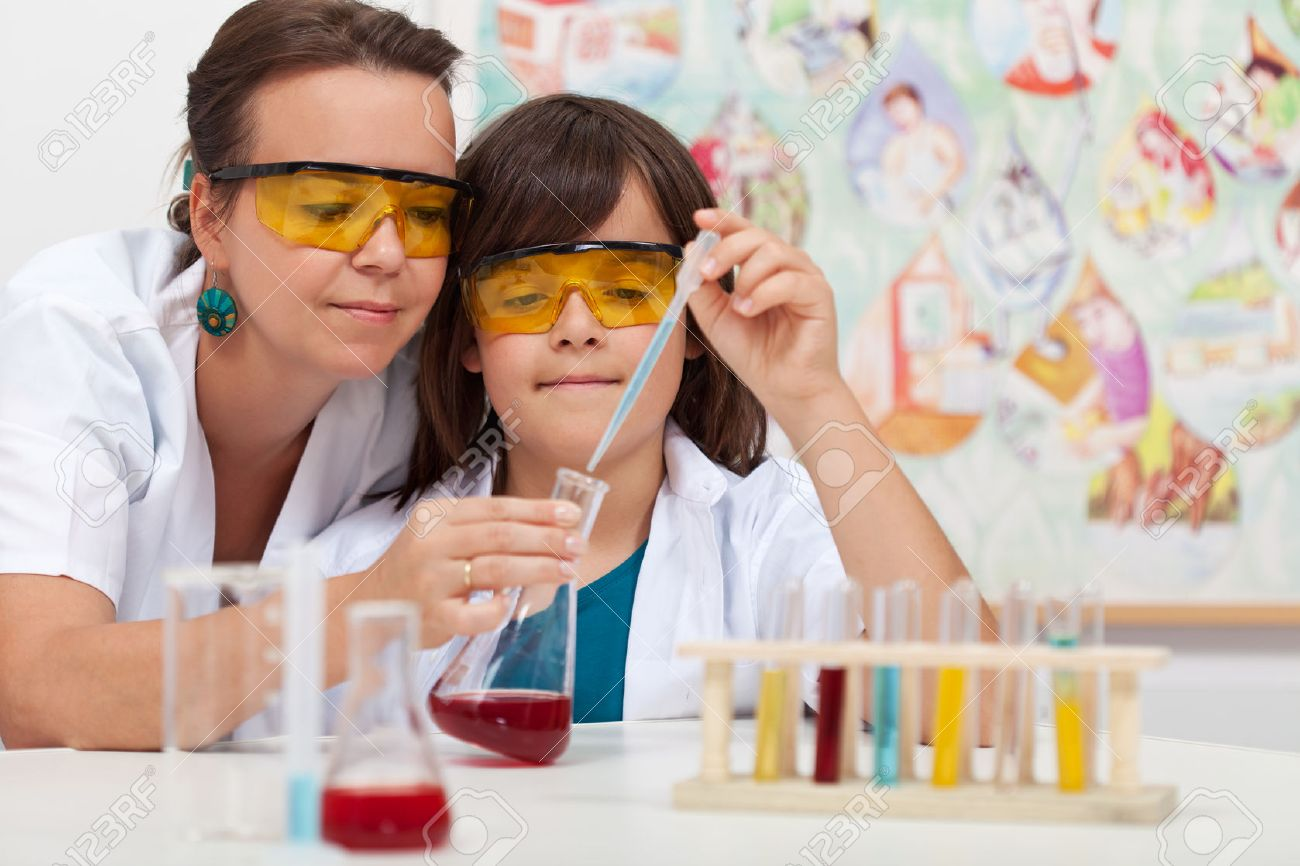Young boy in elementary science class doing chemical experiment helped by teacher - 47114916