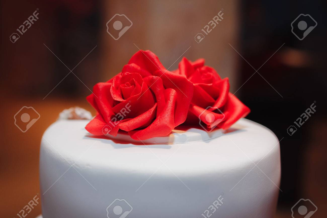 Gorgeous white cake decorated with red flowers roses ribbons gorgeous white cake decorated with red flowers roses ribbons and bow wedding stock mightylinksfo Image collections