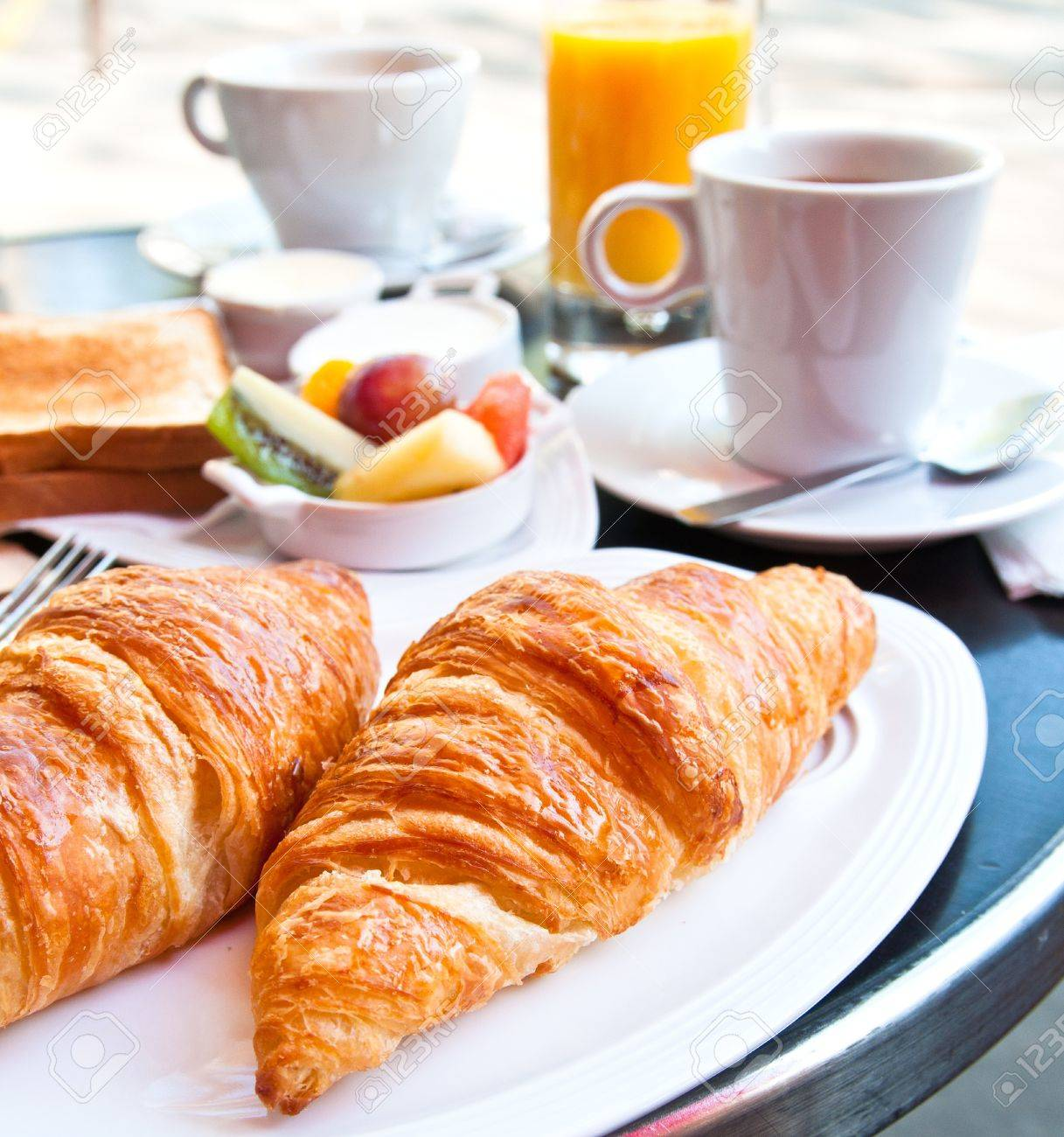 Breakfast with coffee and croissants in a basket on table Stock Photo - 9355395