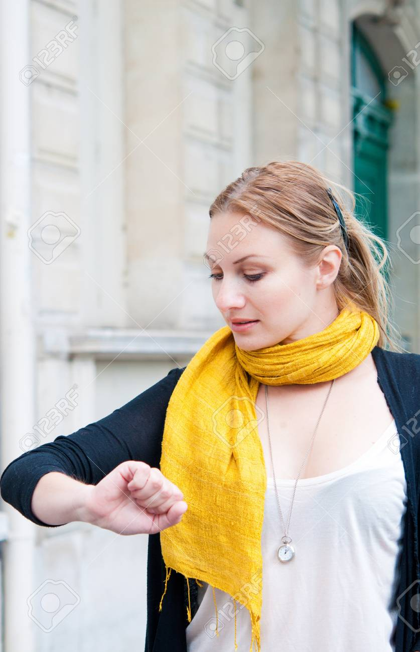 beautiful young woman checking the time on her wrist watch in the streets of Paris Stock Photo - 12847335