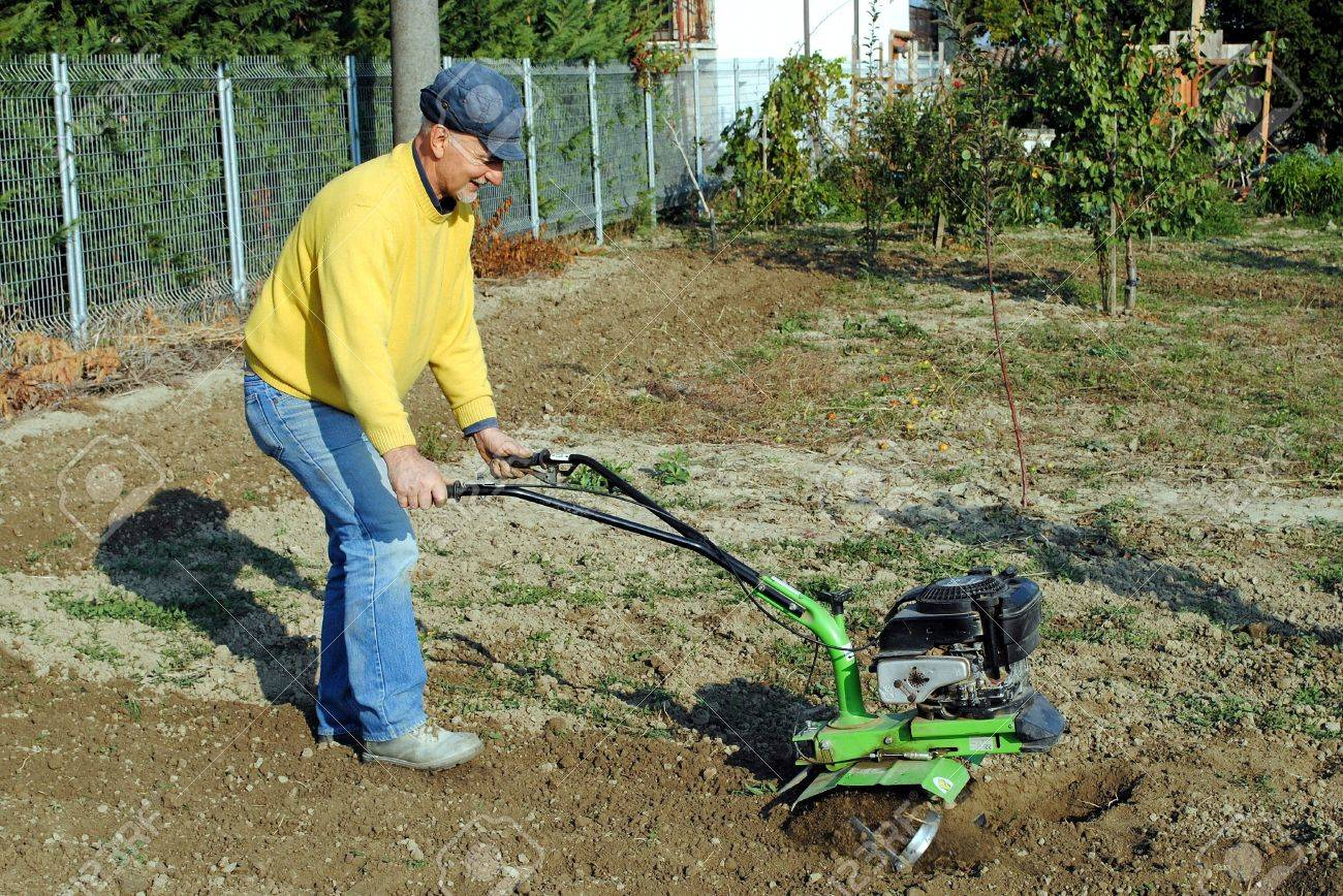 Middle Age Man With A Rototiller In The Garden Stock Photo