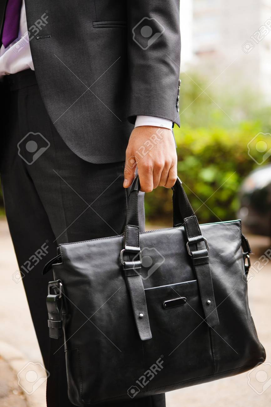 2051f66dc3 Leather suitcase in hand. Person in suit holding men bag Stock Photo -  71710754