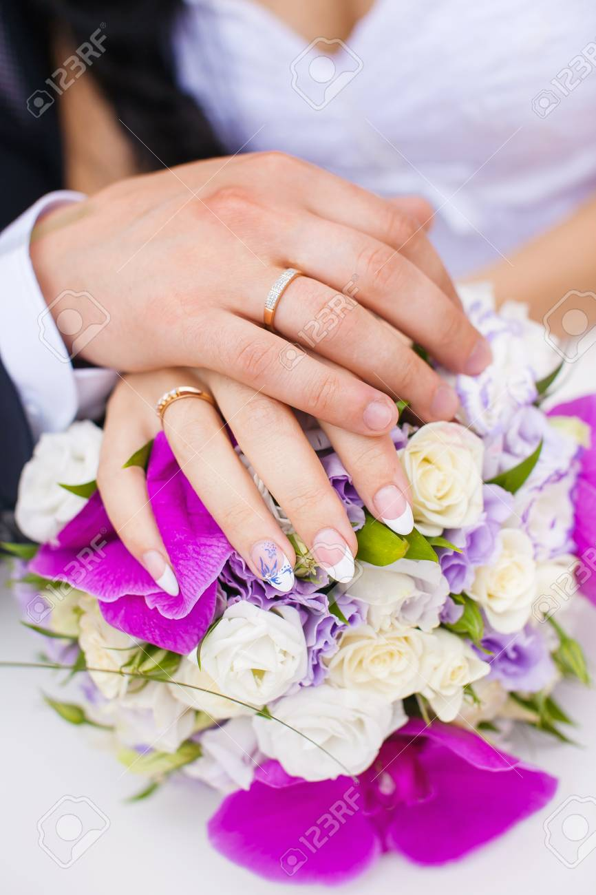 Wedding Rings On Couple Hands On Bridal Bouquet. Stock Photo ...