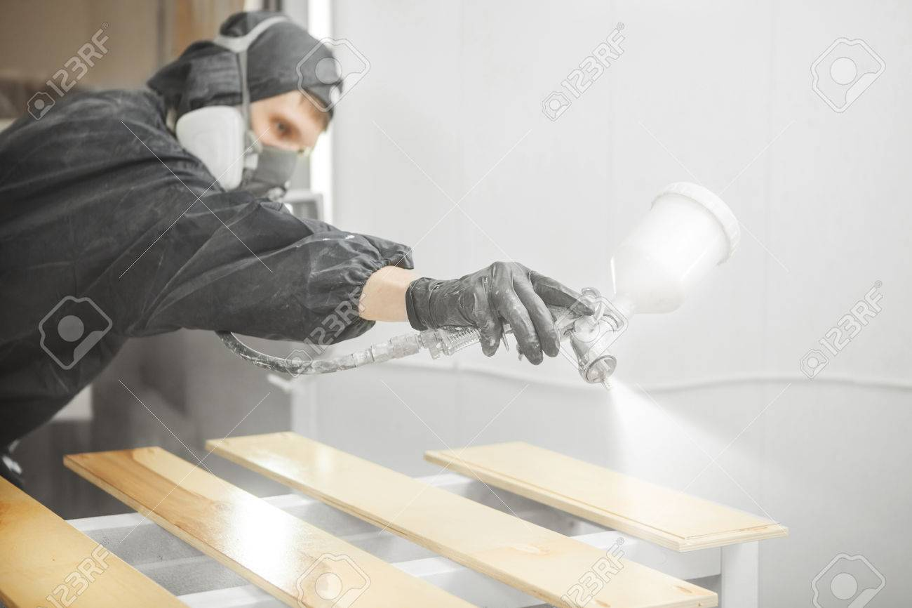 Man in respirator mask painting wooden planks at workshop. - 81810771