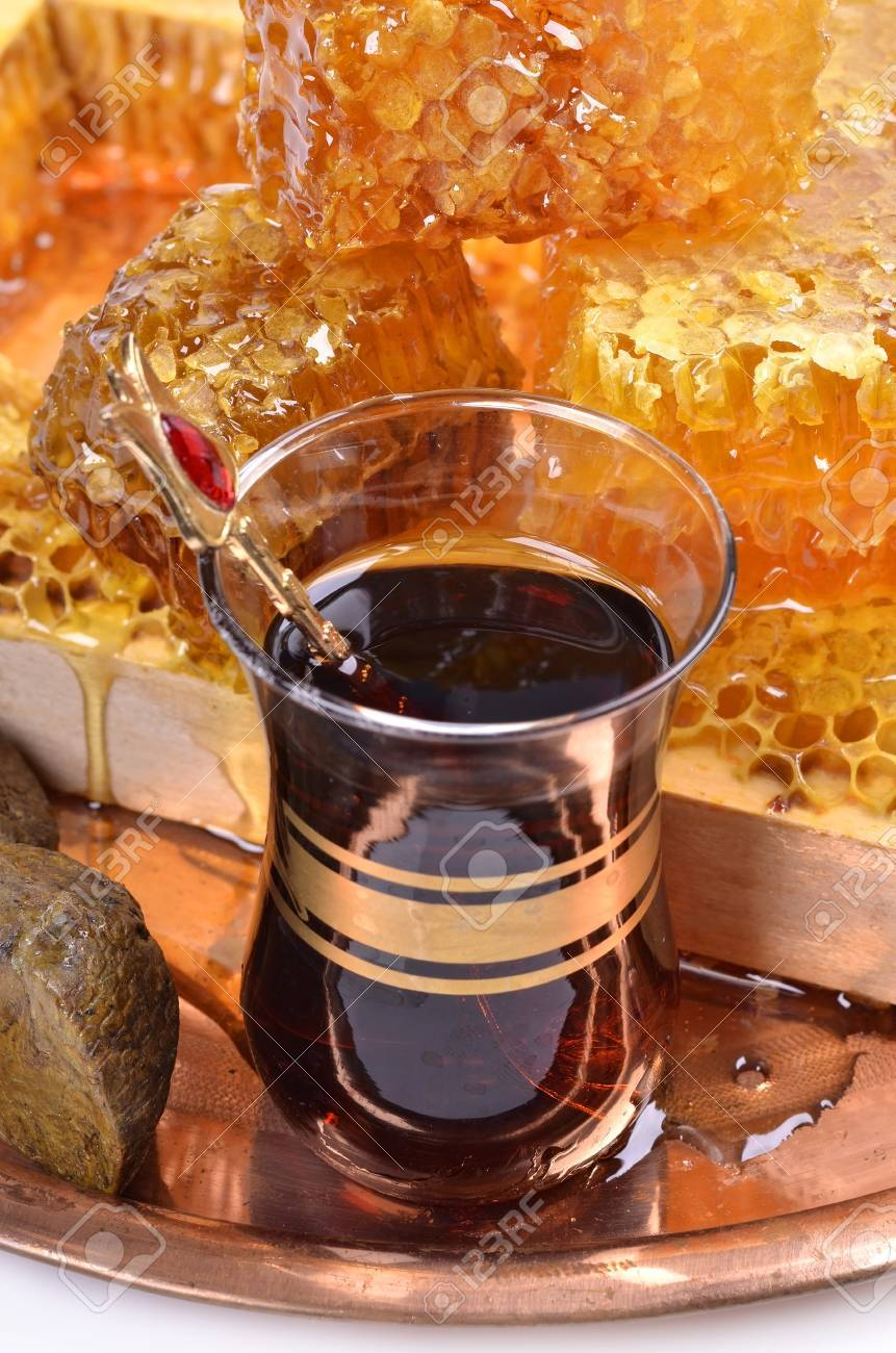 fresh  honeycombs  and wooden stick ,cup of Turkish tea,propolis, isolated on white background Stock Photo - 22396265