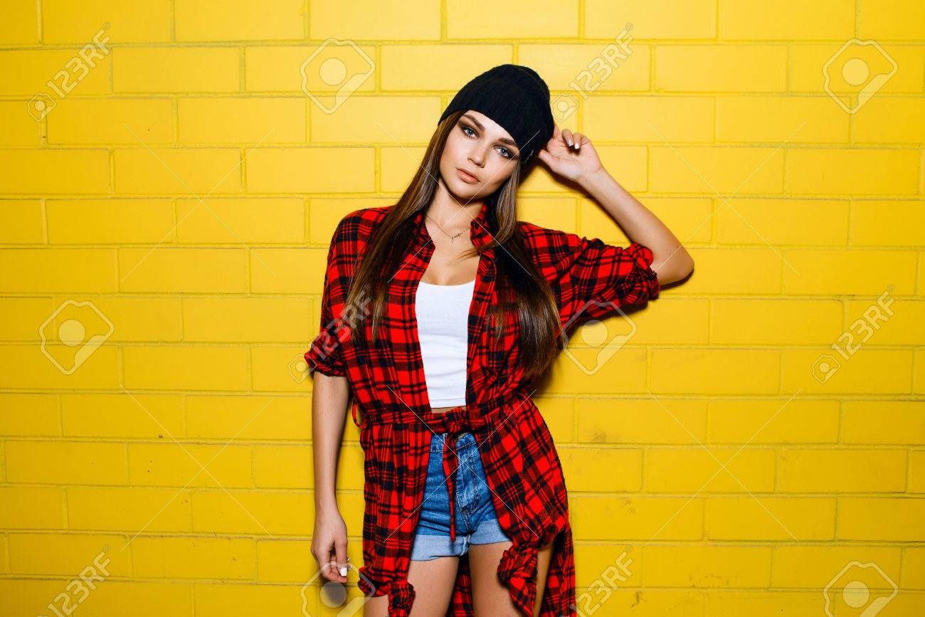 b63a35855e1d15 Beautiful young sexy hipster girl posing and smiling near yellow wall  background in red plaid shirt