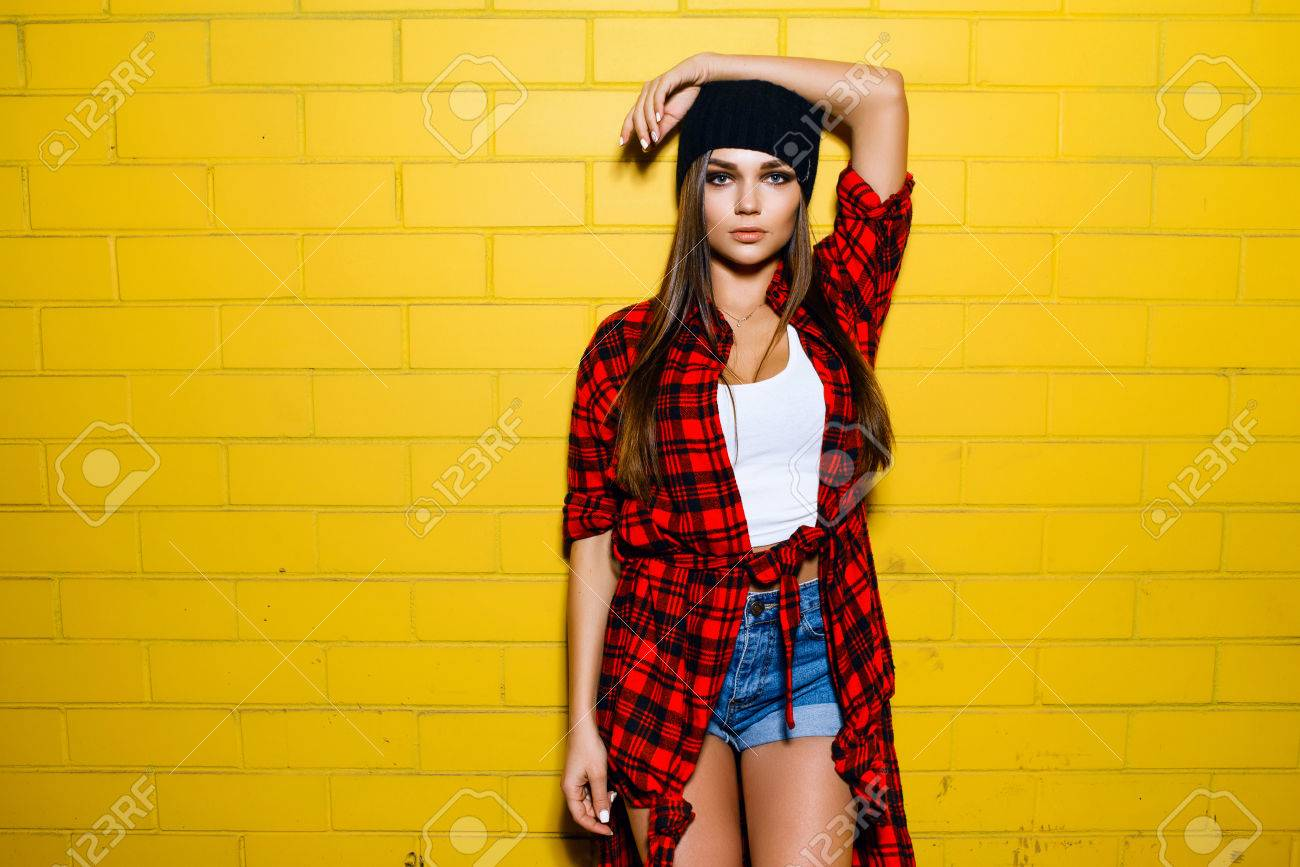 1fdb19cf9e5 Beautiful young sexy hipster girl posing and smiling near urban yellow wall  background in red plaid
