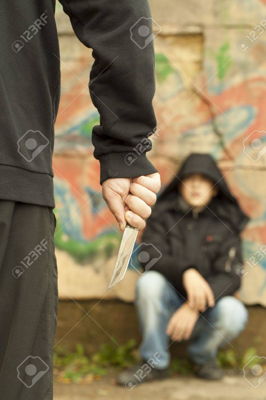 Boy looks at a man with a knife Stock Photo - 15895550