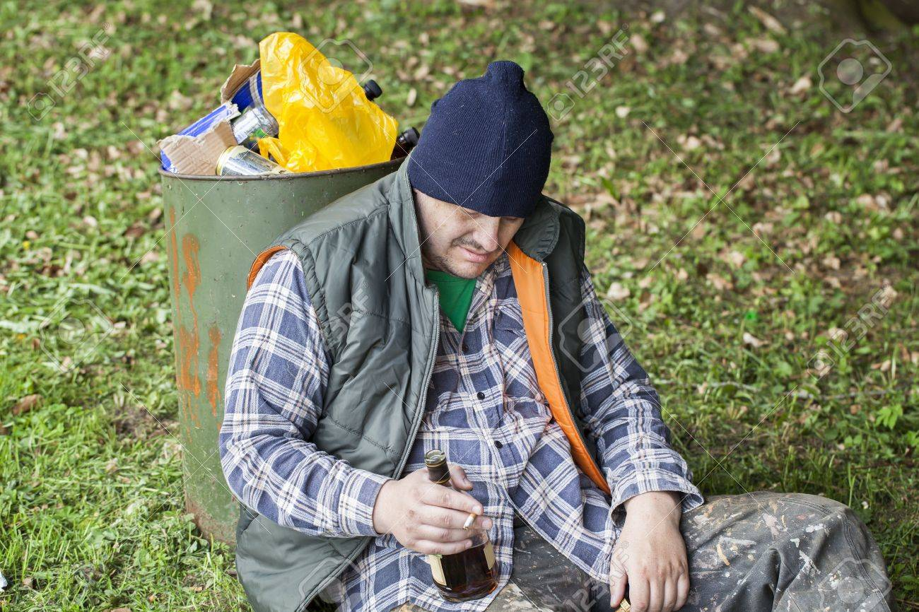 Homeless with botle of drink in hand leaning against garbage bin in the park Stock Photo - 16881474