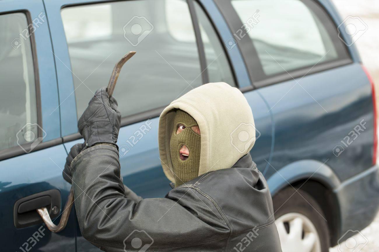 Robber with a crowbar near the car door Stock Photo - 17214620
