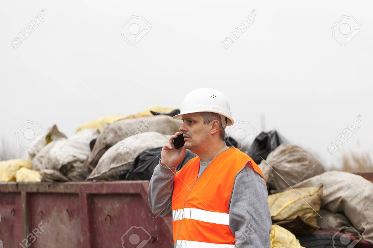 Worker with cell phone near garbage and container Stock Photo - 17625656