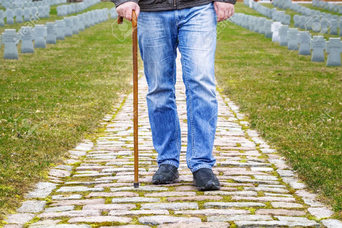 Man with walking stick in cemetery - 27830840