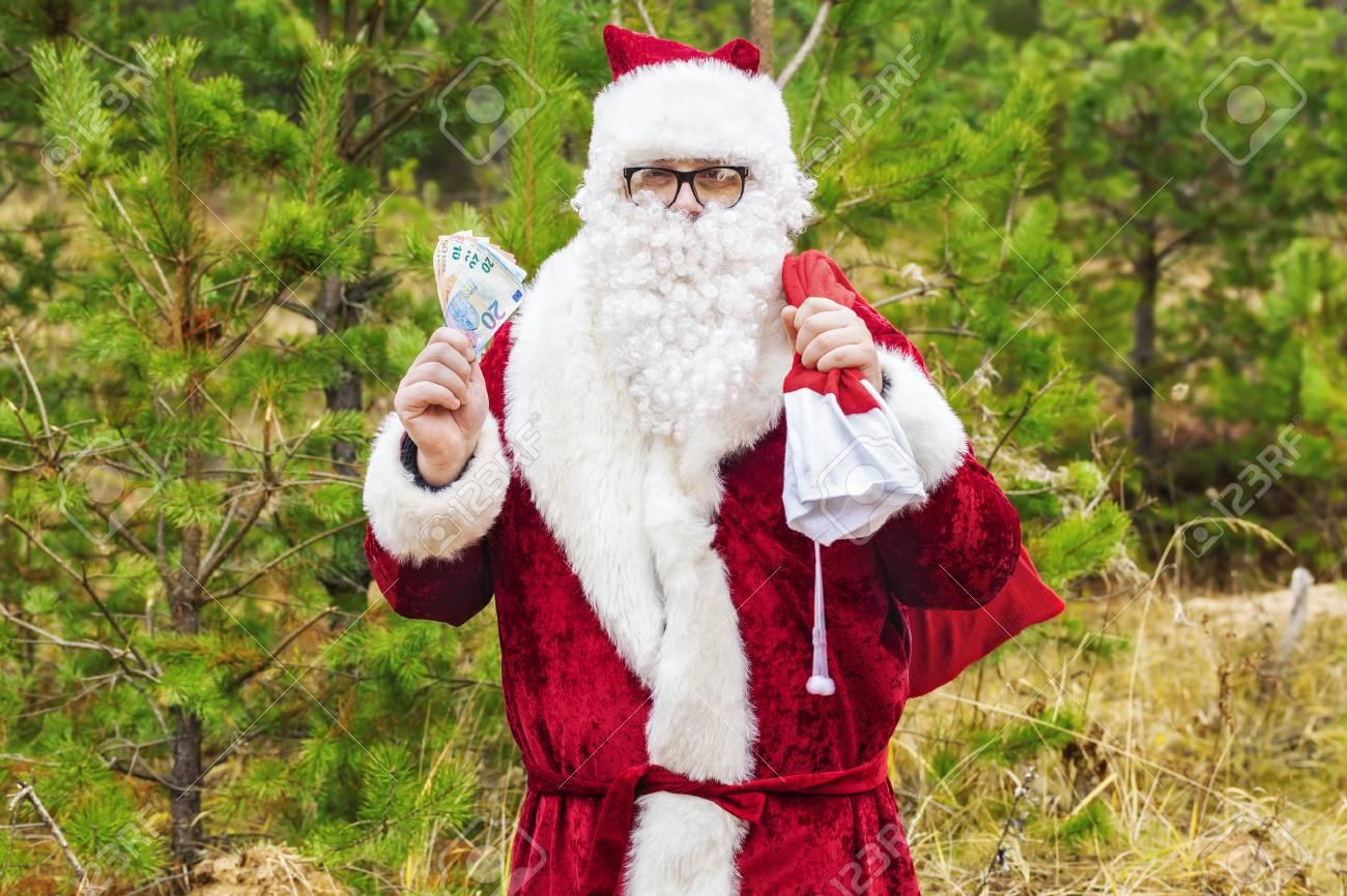 Banque d images - Père Noël avec des billets en euros et sac cadeau en forêt d8ffba10811