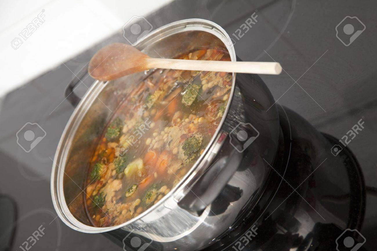Boiling pot of soup on top of the stove. Focus across the middle of image. Stock Photo - 8385094
