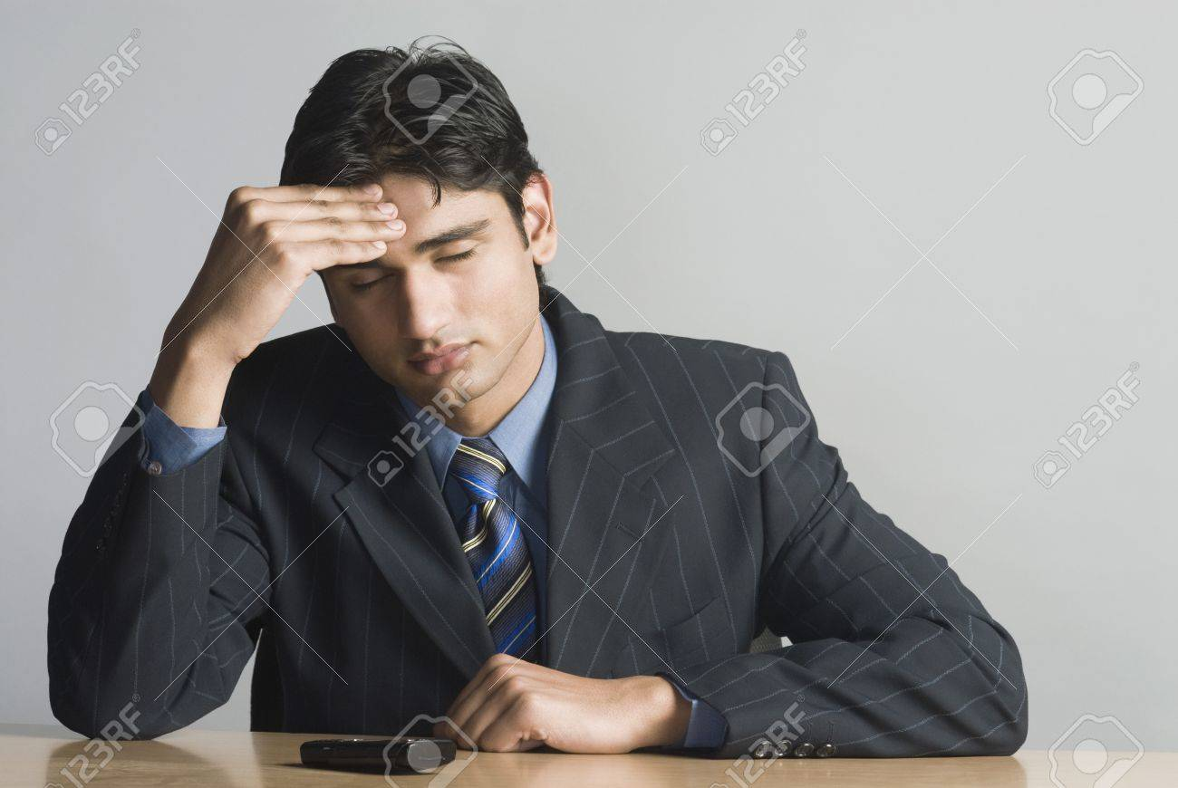 Businessman rubbing his forehead Stock Photo - 10169544