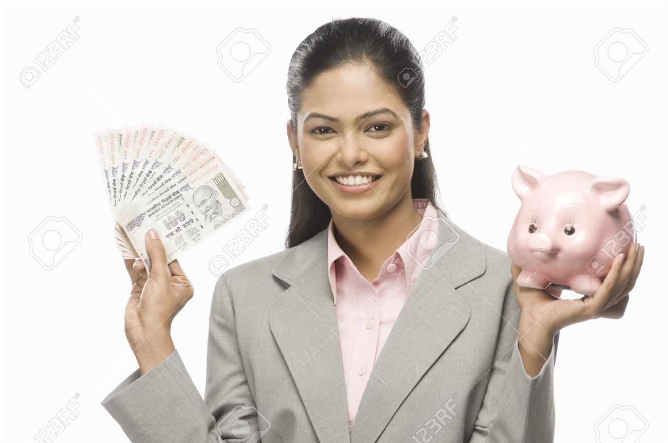 Portrait of a businesswoman showing Indian paper currency and a piggy bank Stock Photo - 10169531