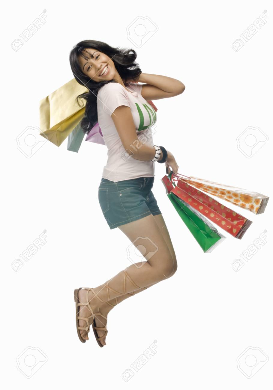 Young woman carrying shopping bags and jumping Stock Photo - 10126324