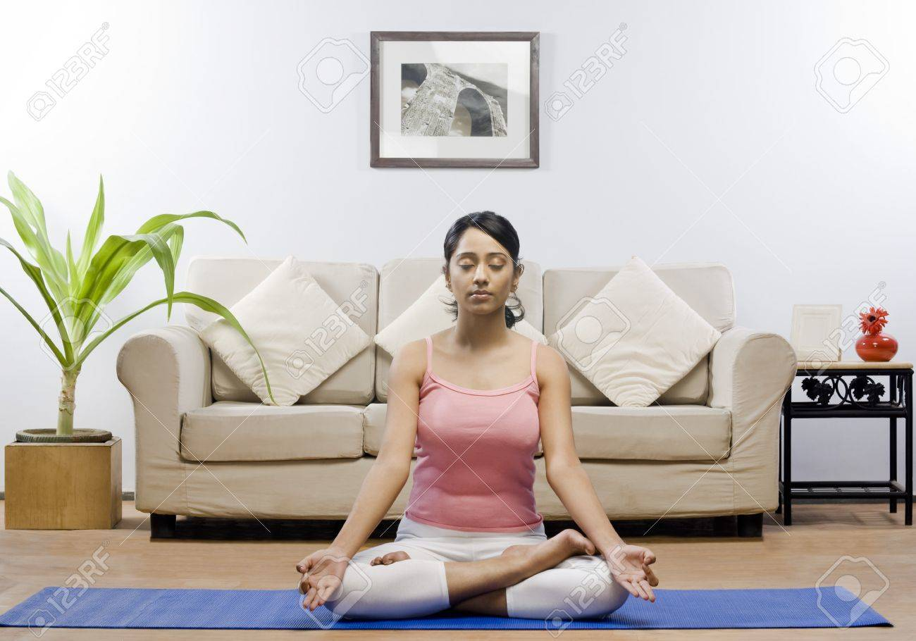 Young Woman Meditating In A Living Room Stock Photo