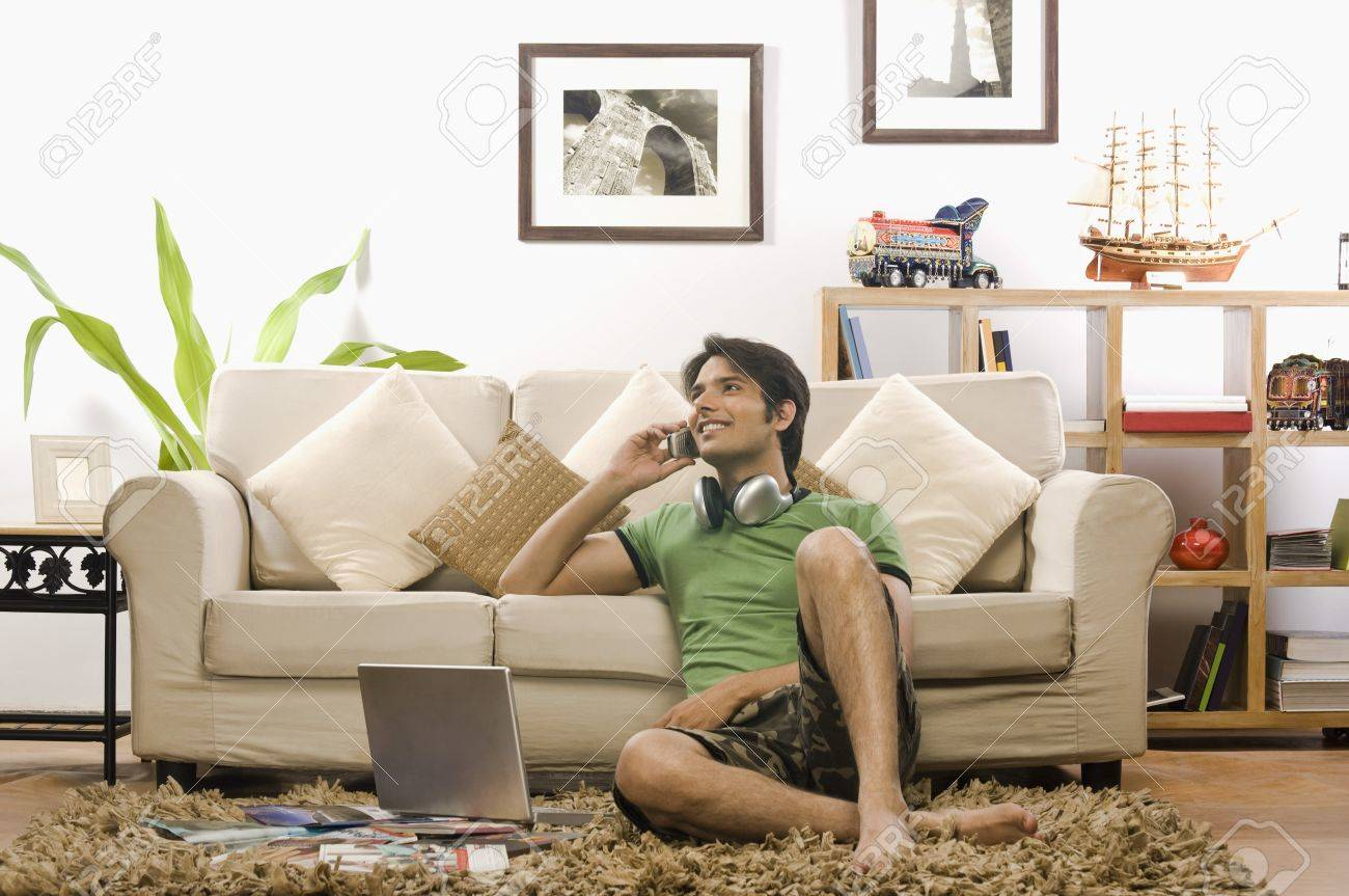 Young man talking on a mobile phone in the living room Stock Photo - 10123758