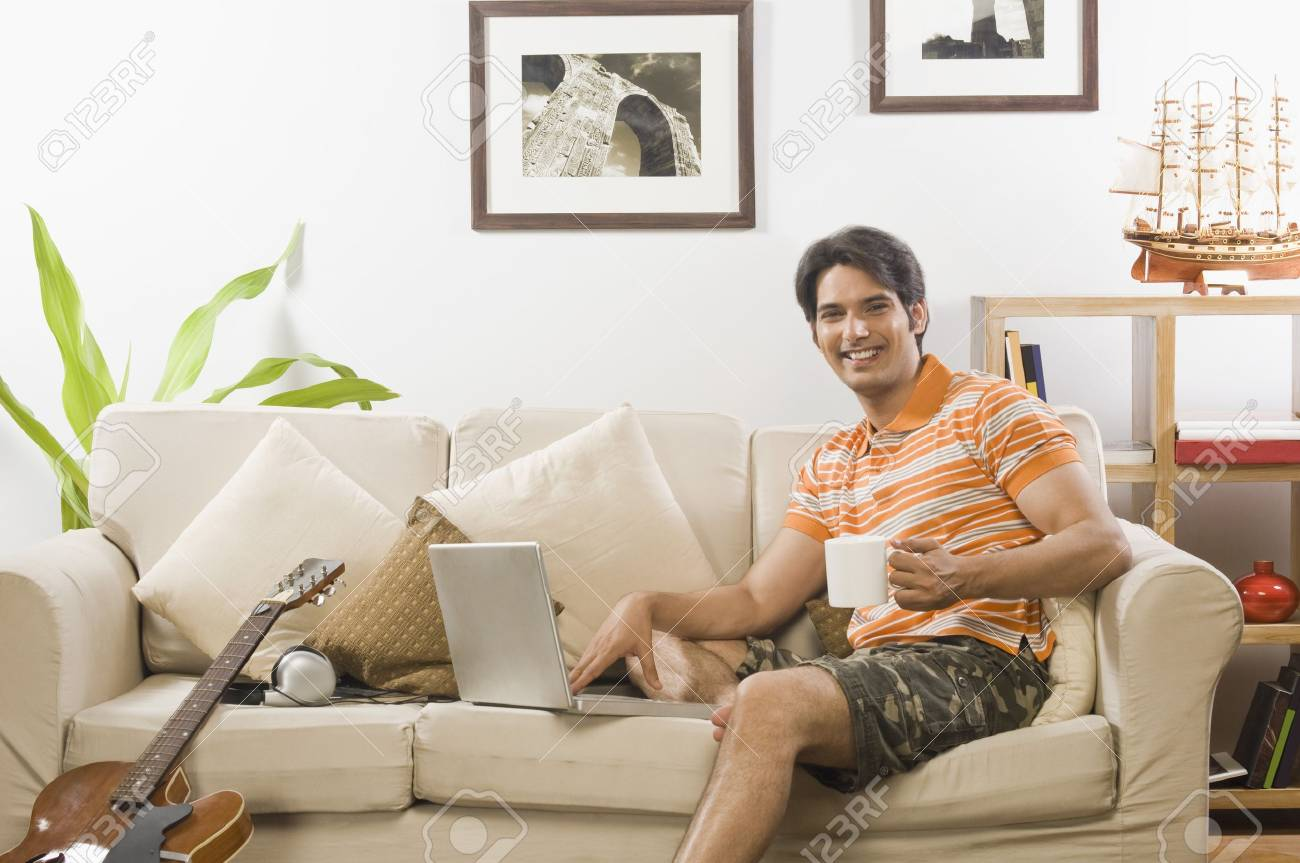 Young man holding a coffee mug in the living room - 10123744