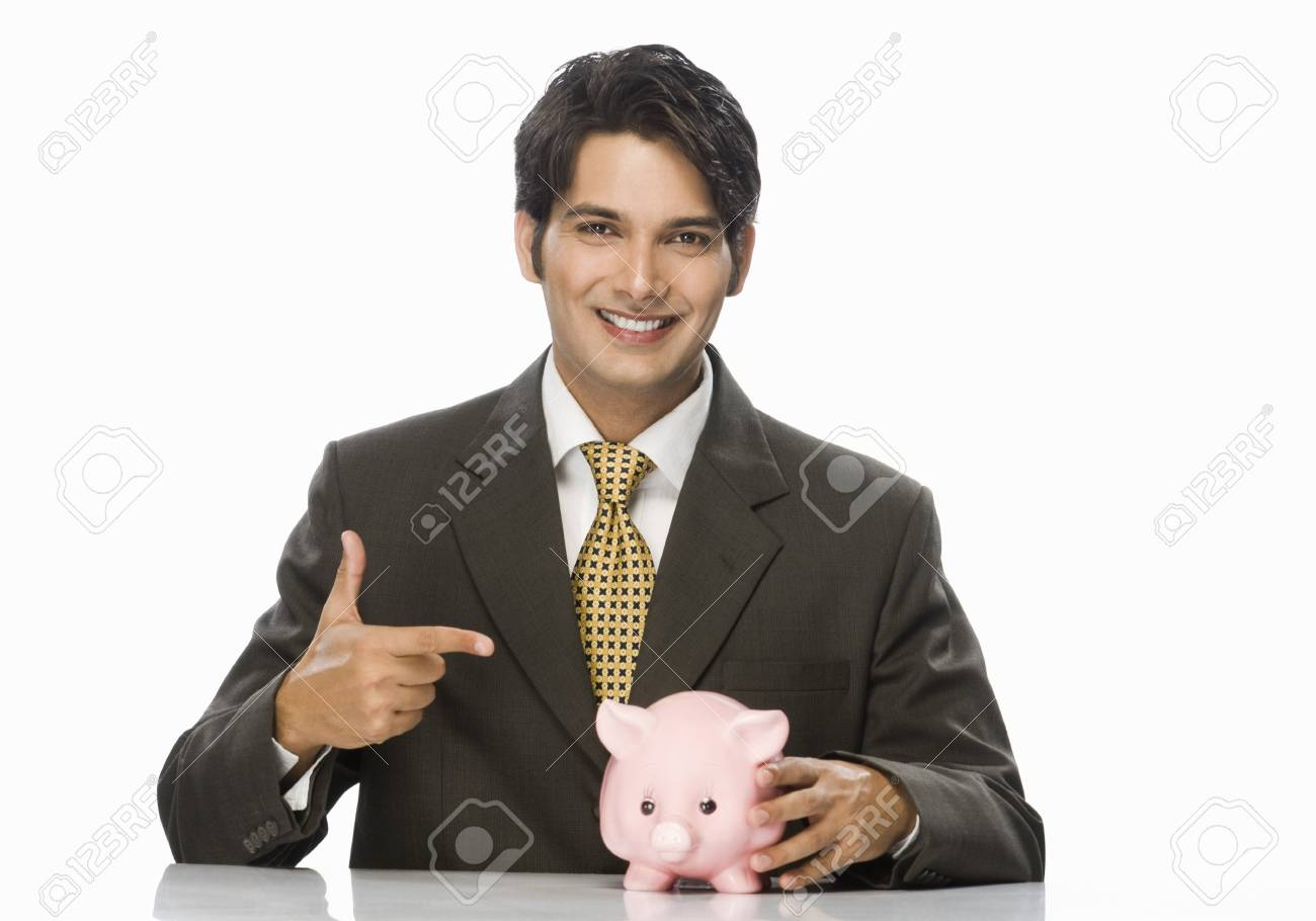 Portrait of a businessman pointing towards a piggy bank Stock Photo - 10126130