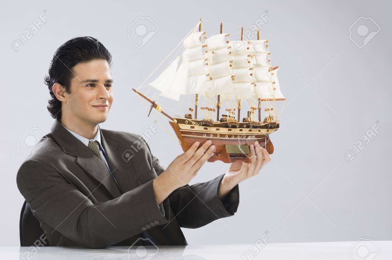 Businessman looking at a model ship Stock Photo - 10123735