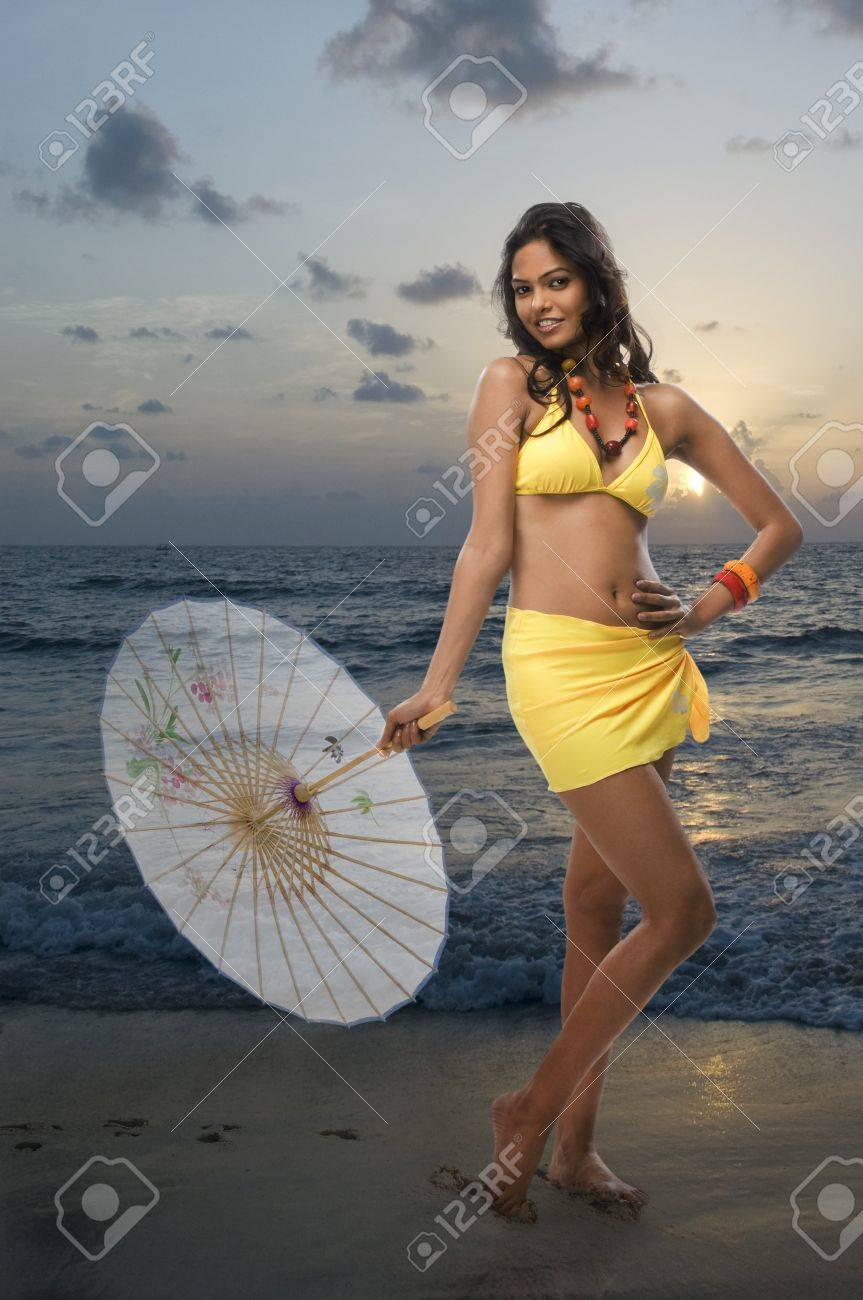 Portrait of a female fashion model holding a parasol on the beach Stock Photo - 10124848