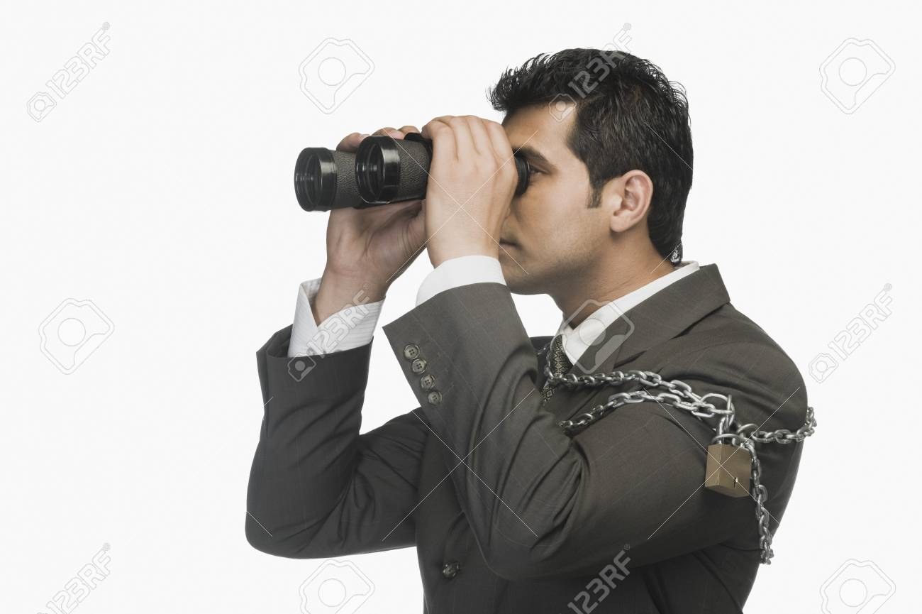 Businessman locked in chains and looking through binoculars Stock Photo - 10124475