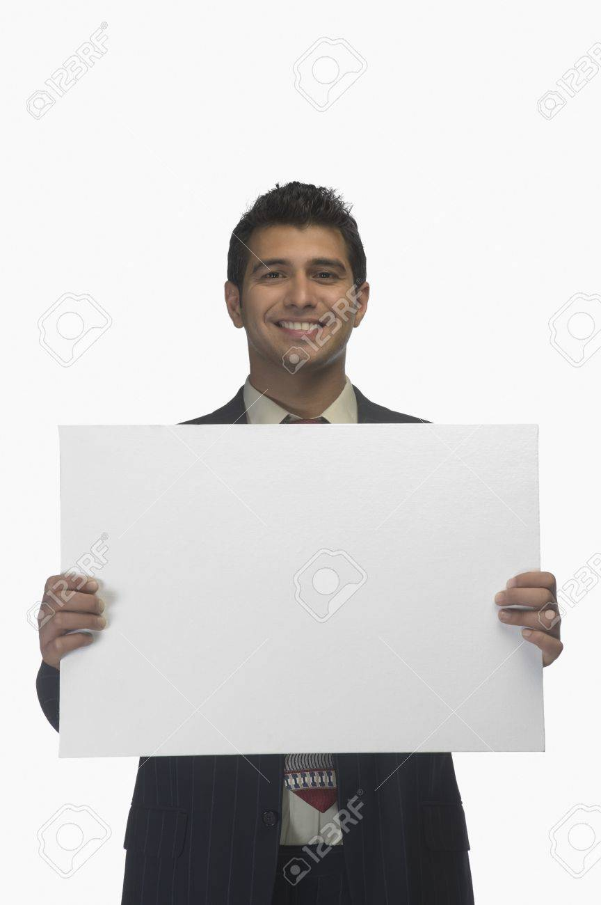 Portrait of a businessman holding a blank placard and smiling Stock Photo - 10124065