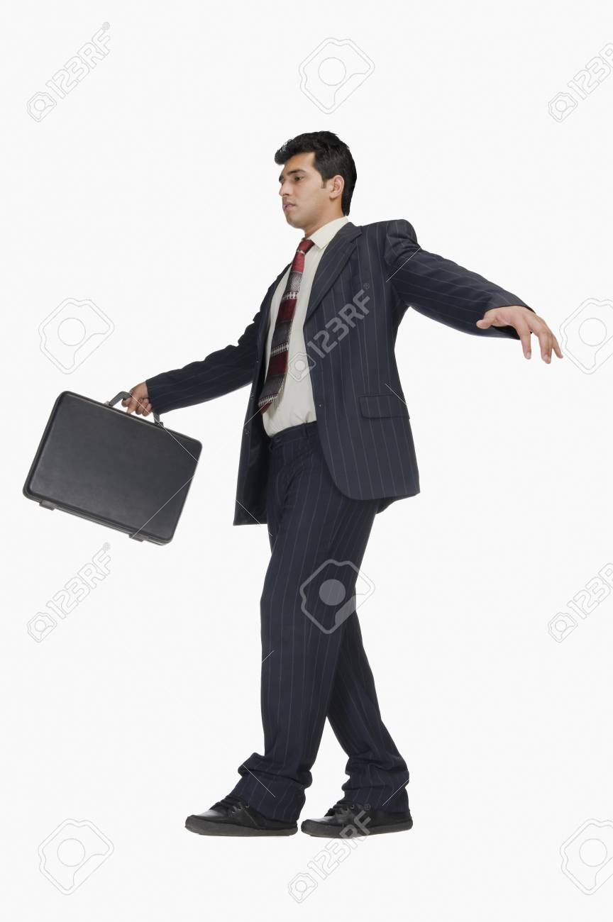 Businessman holding a briefcase and walking carefully Stock Photo - 10123939