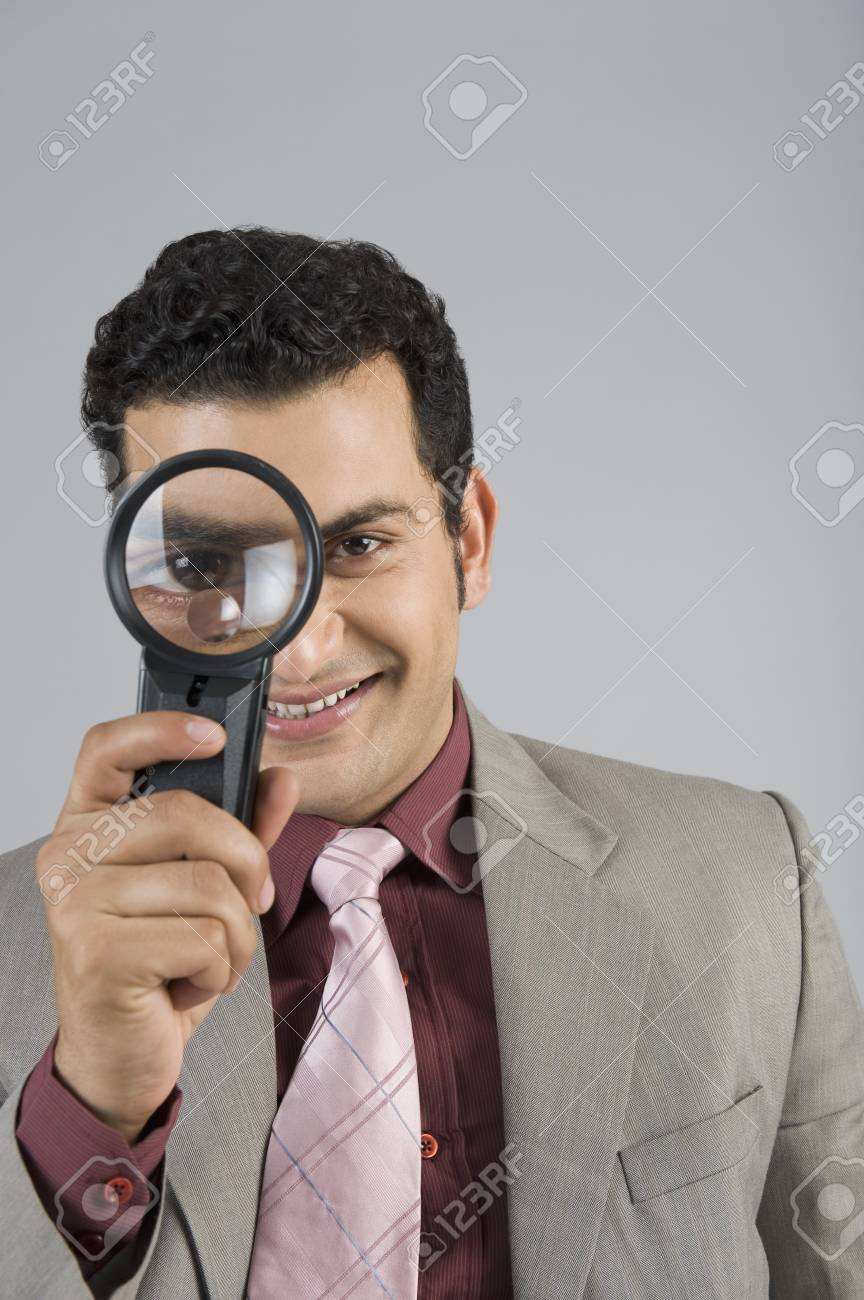 Businessman looking through a magnifying glass Stock Photo - 10166677