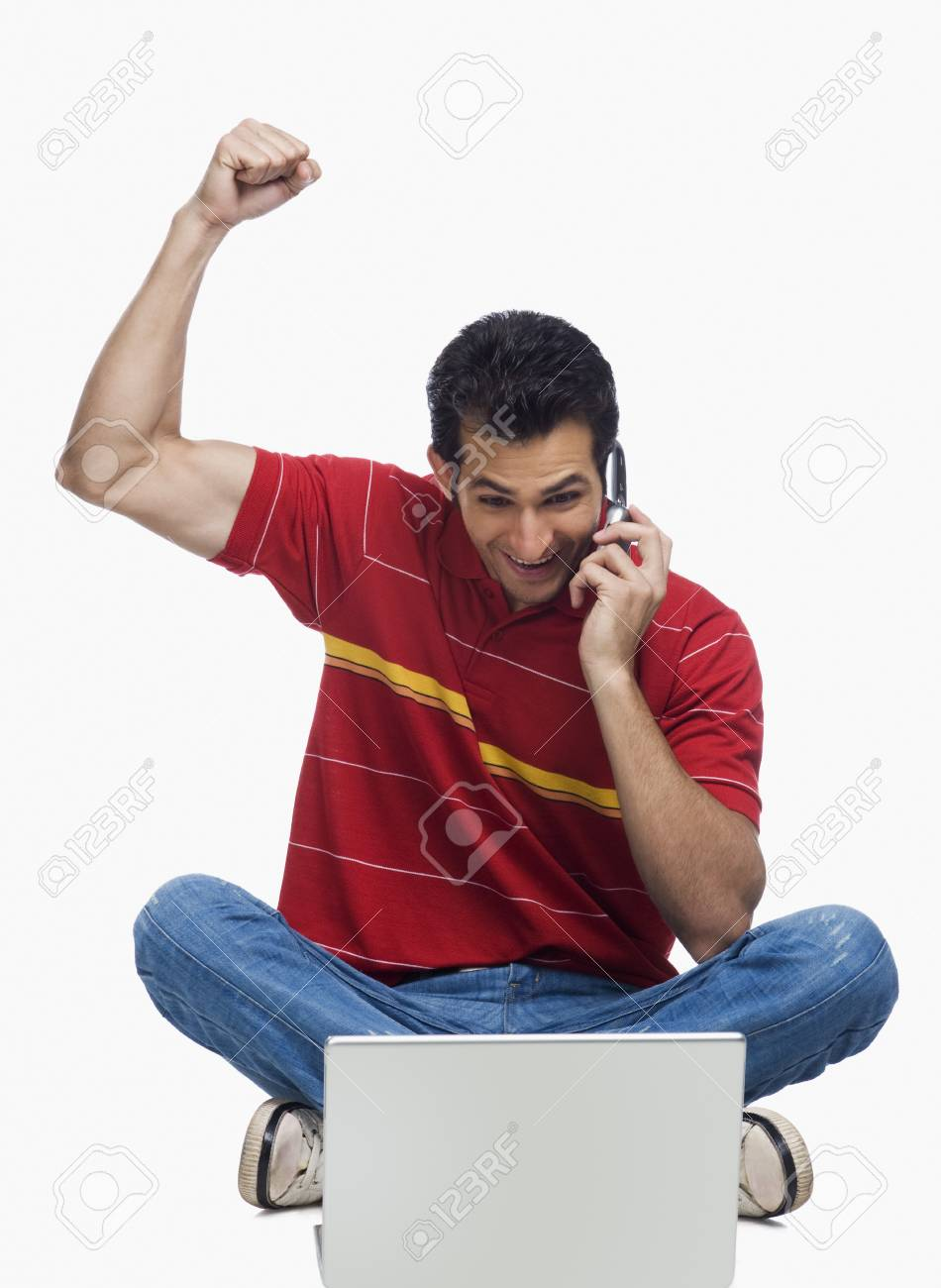 Man cheering in front of a laptop while using a mobile phone Stock Photo - 10125231