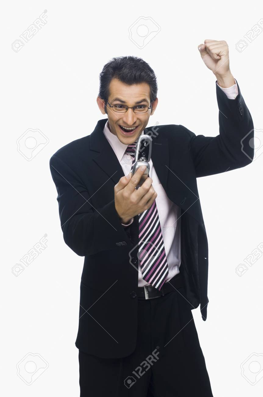 Businessman clenching fist while reading a text message on a mobile phone Stock Photo - 10124219