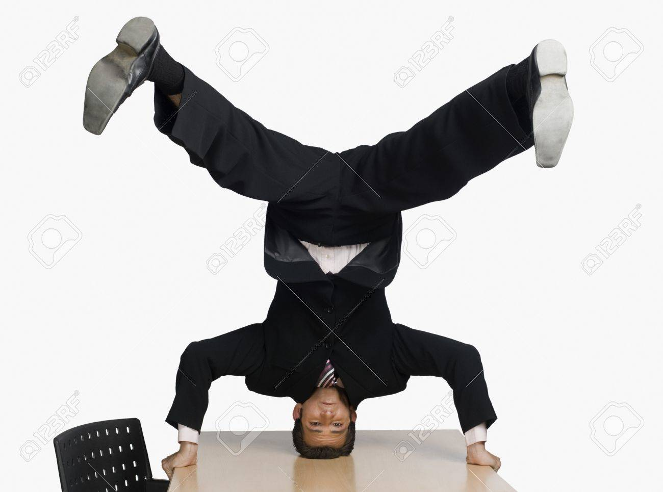 Businessman doing headstand on a conference table Stock Photo - 10123945