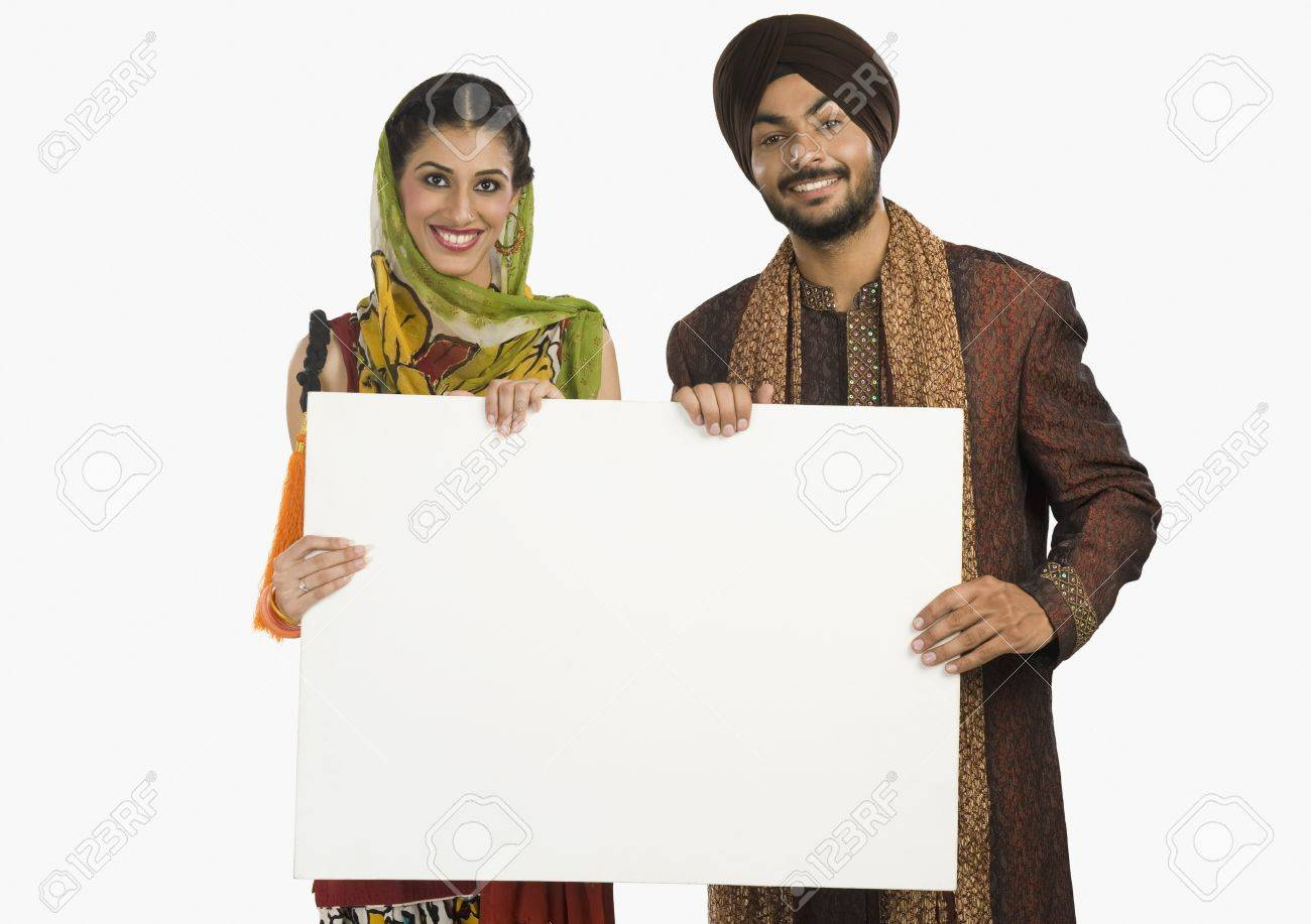 Portrait of a Sikh couple holding a blank placard Stock Photo - 10125386