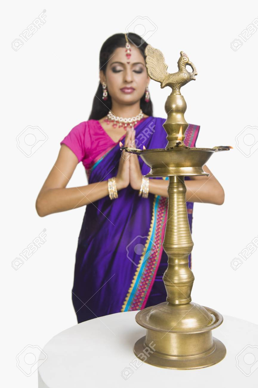 Woman praying with oil lamp in front of her Stock Photo - 10124104