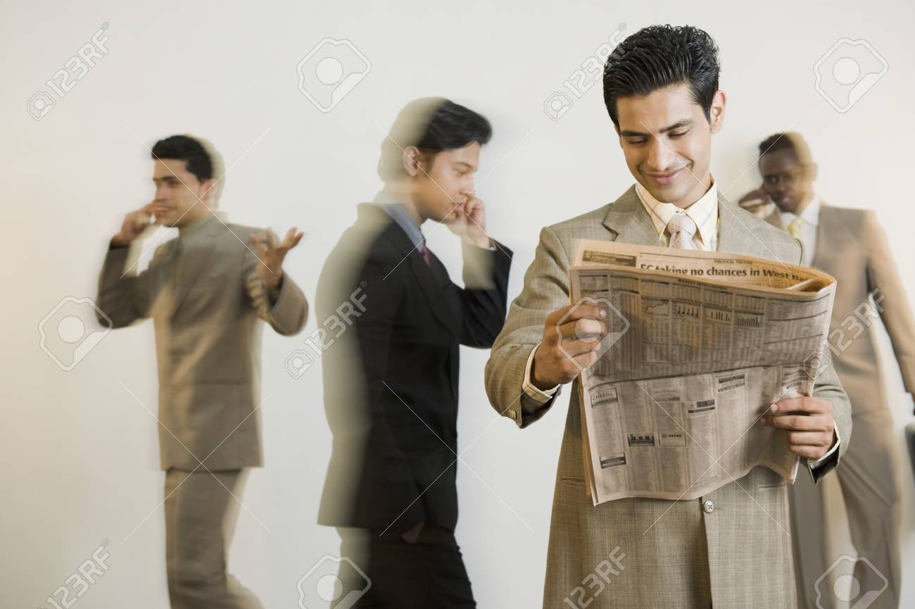 Businessman reading a newspaper with his colleagues in the background Stock Photo - 10125251