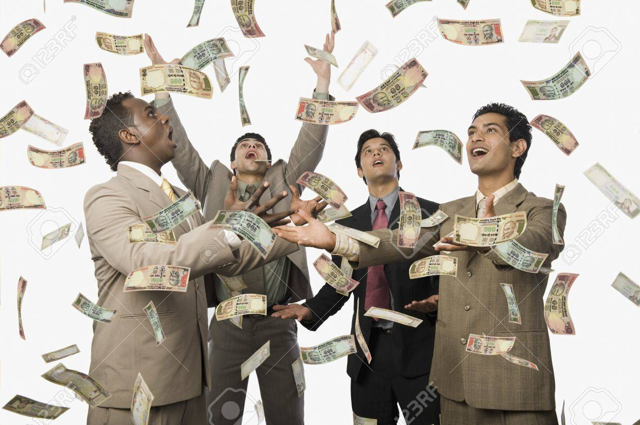 Banknotes falling over four businessmen Stock Photo - 10169146