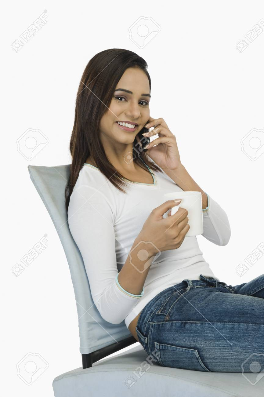 Woman talking on a mobile phone and drinking coffee Stock Photo - 10125104