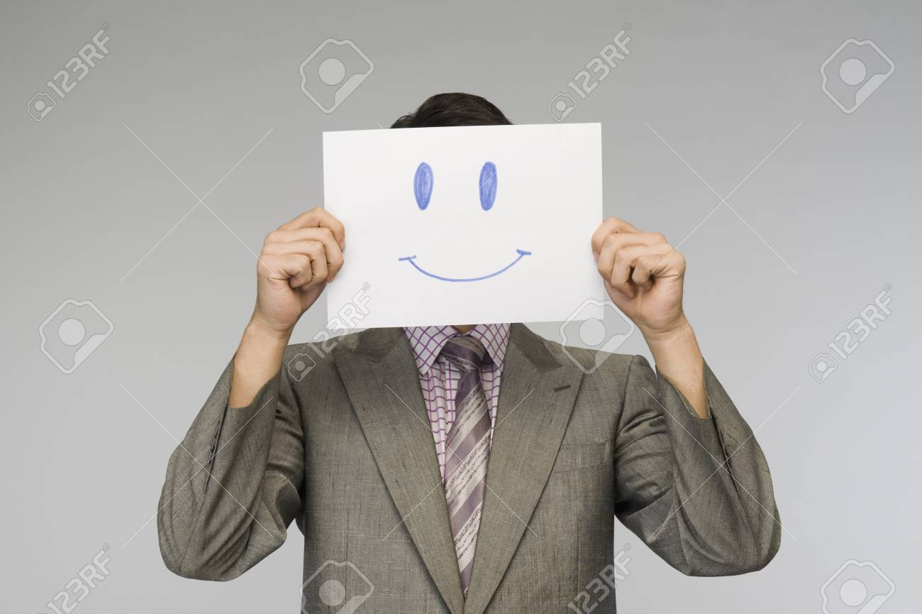 Businessman holding a smiley face paper in front of his face Stock Photo - 10167968
