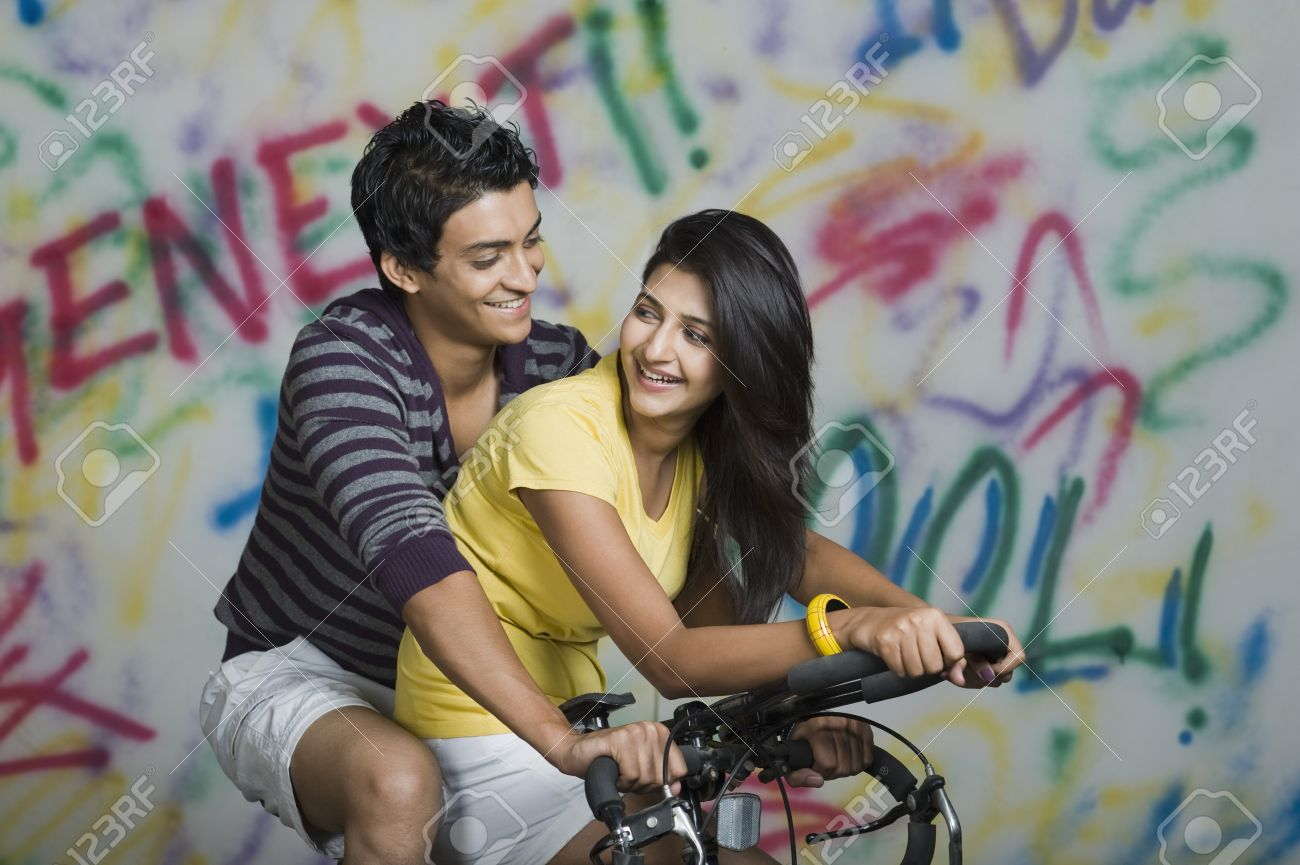 Couple Riding A Bicycle And Smiling Stock Photo Picture And Royalty