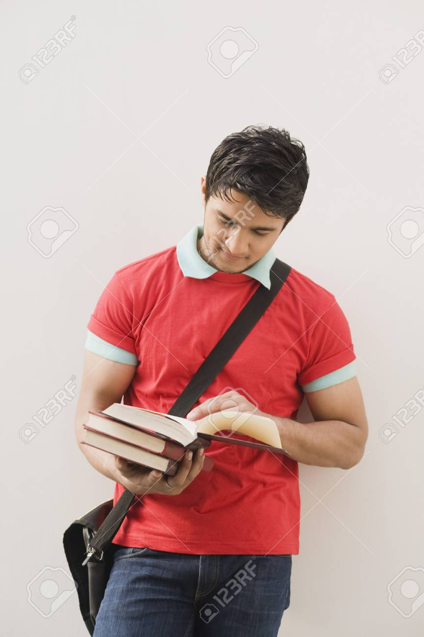 Man leaning against a wall and reading a book Stock Photo - 10167357