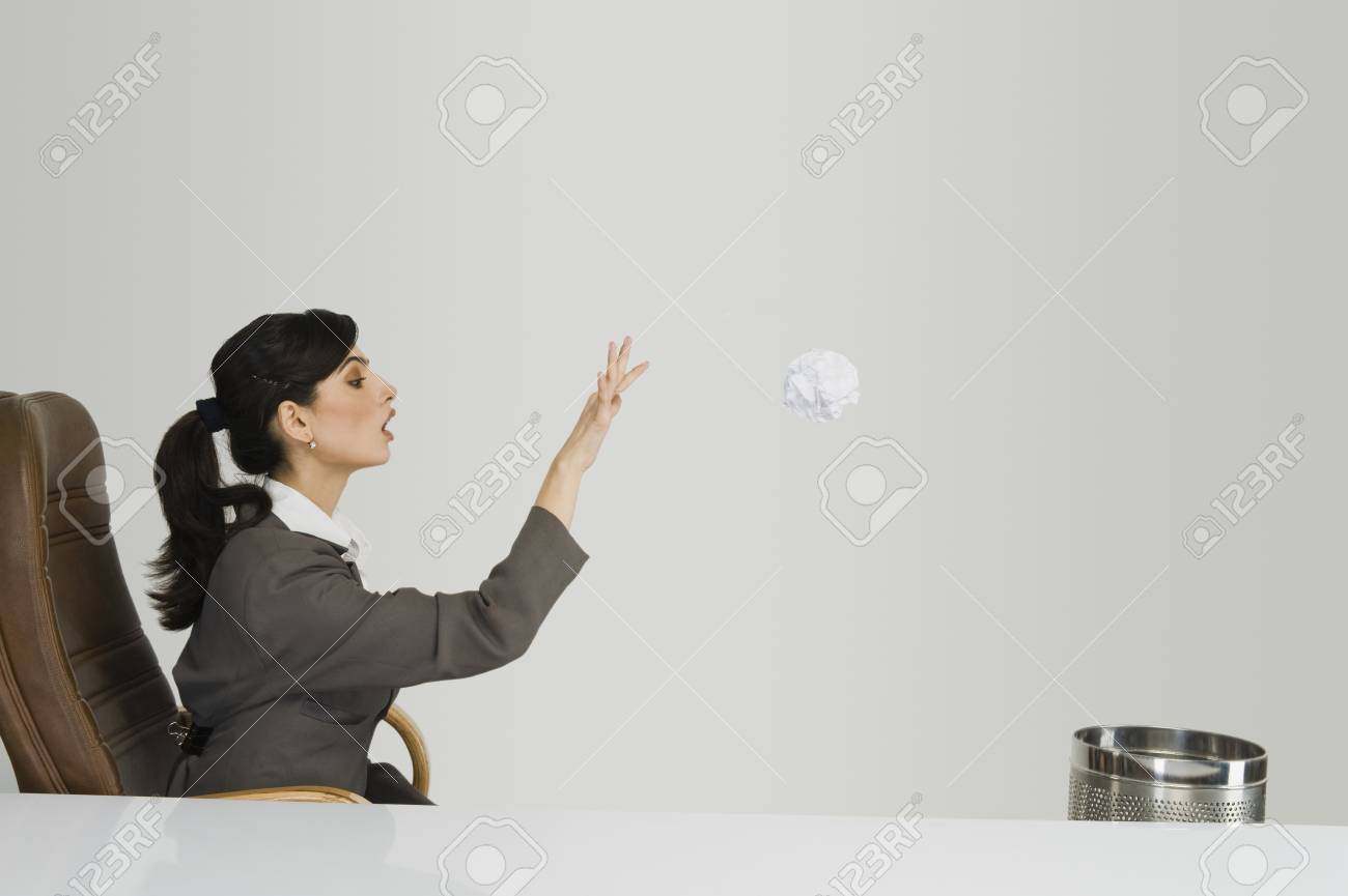 Businesswoman throwing crumpled paper into a wastepaper basket Stock Photo - 10168778