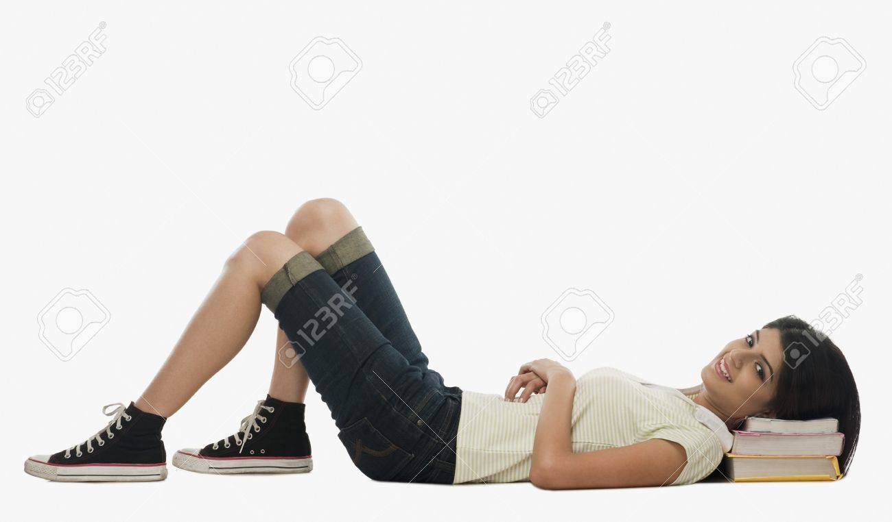 Female university student resting on a stack of books Stock Photo - 10168918