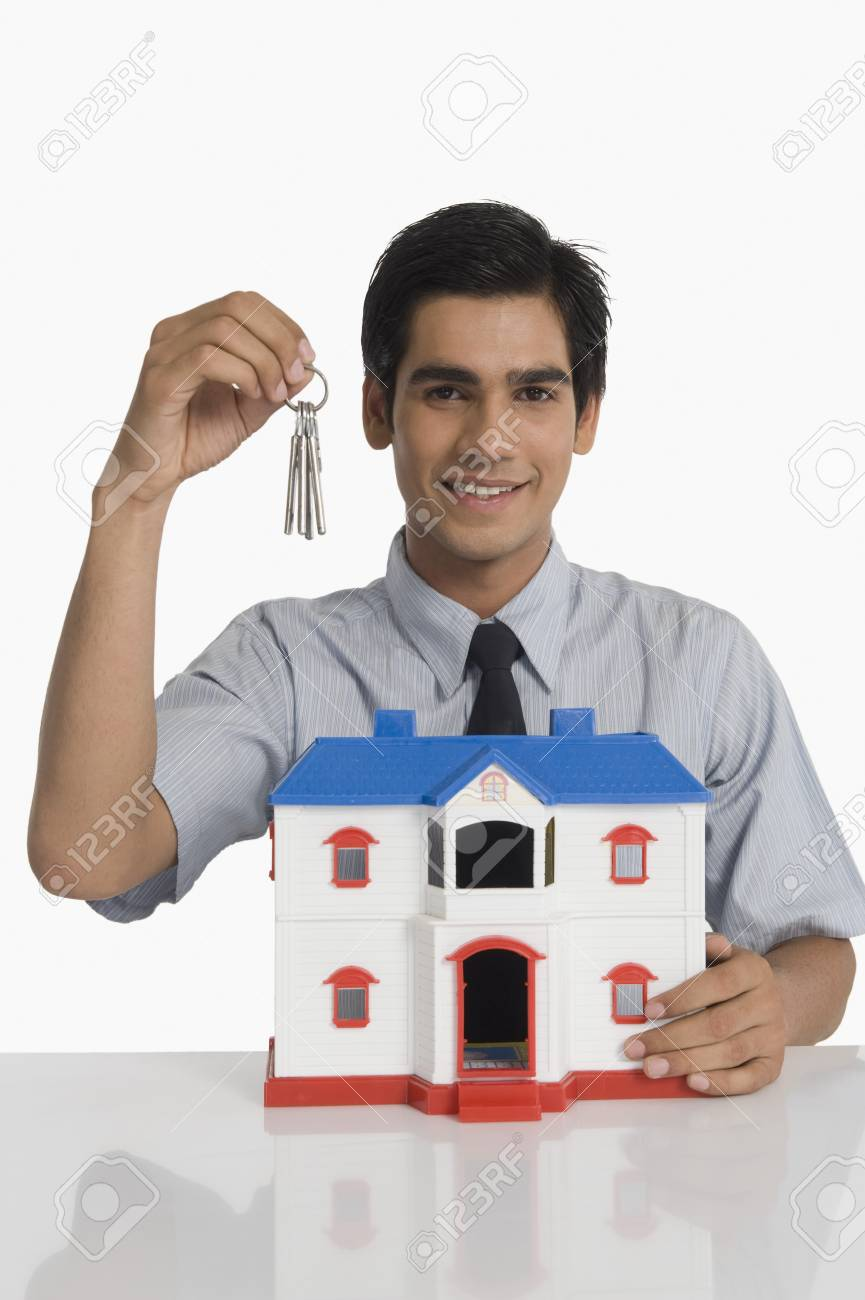 Real estate agent holding keys and a model home Stock Photo - 10168535